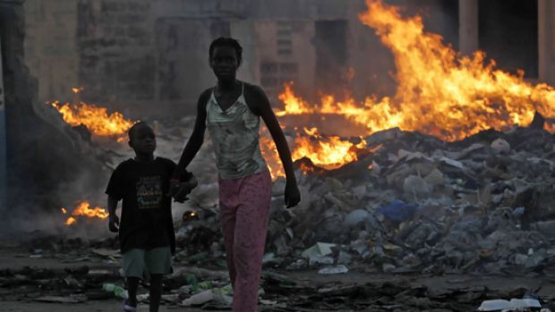 Survivors of Haiti's earthquake walk along a dump near the centre of Port-au-Prince.