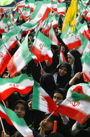 Iranian schoolgirls wave flags and anti-US placards at a rally to mark the anniversary of the Islamic revolution in Tehran.