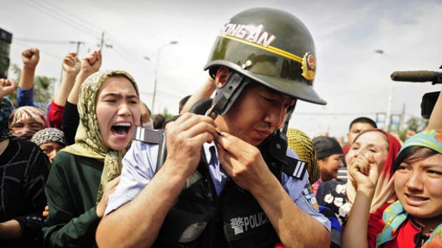 Mass unrest … Uighur women surround a Chinese riot policeman during protests in Urumchi, the capital of Xinjiang ...