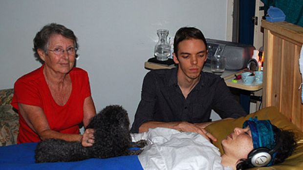 Theda's partner Blake Graham, mother Carol Adams and family dog Maggie keep a vigil at the bedside of her Willetton house.