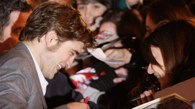 British actor Robert Pattinson signs autographs as he arrives on the red carpet for the UK premiere of Remember Me.
