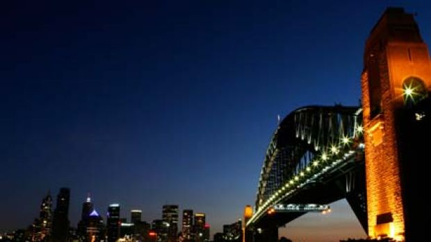 This combination picture shows views of the Sydney Harbour Bridge with the lights on (top) before Earth Hour, and then ...