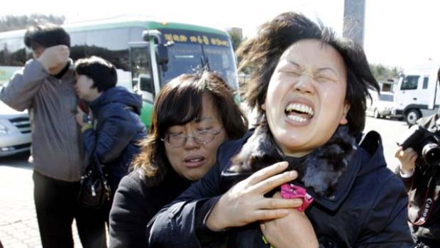 Cover-up charge … relatives cry out at the naval base at Pyeongtaek.
