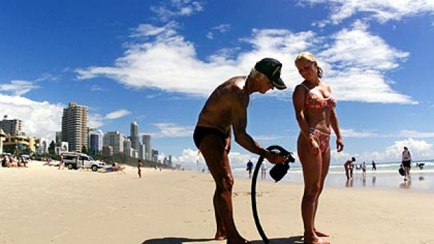 Al Baldwin sprays a beachgoer with sunscreen at Surfers Paradise, where he held court for 30 years.