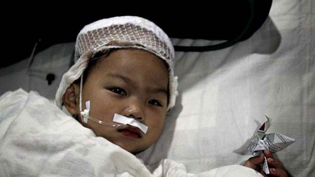 Survivor ... a child injured in the Hanzhong killings leaves intensive care with a paper crane, signifying recovery from ...