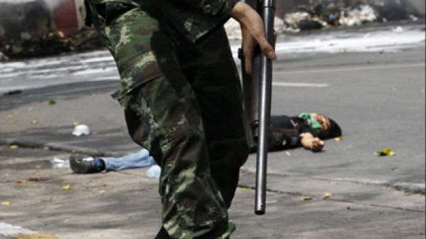 Fight to the death...a soldier walks past a body in Bangkok as troops moved in to end the anti-government protest.