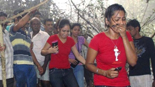 Local residents react after seeing the site of a plane crash in Mangalore in which 159 people are believed to have died.