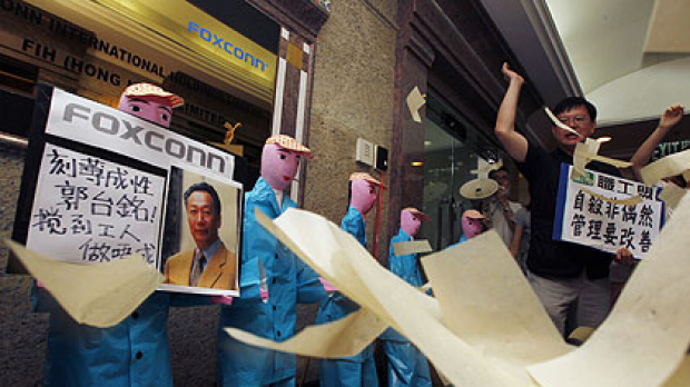 Protesters from several workers' rights groups throw paper money in front of paper figures, depicting workers who ...