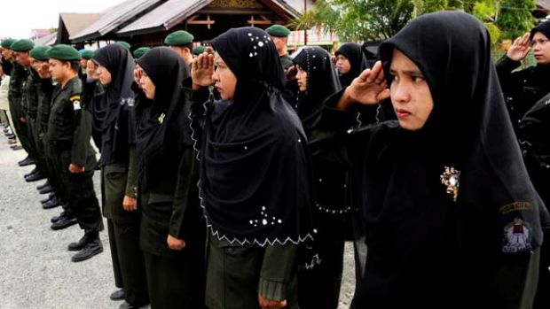 Crackdown ... religious police parade before patrolling the streets of Meulaboh, below, to enforce the Islamic ban on jeans.