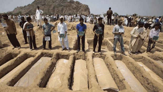 Members of the Ahmadi community stand over the graves of people slain in the attacks on two mosques.