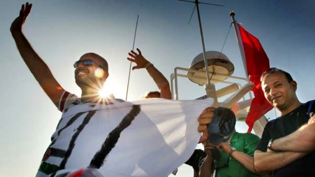 Activists on the Amal passenger boat wave farewell as they set sail from Aghios Nikolaos in Crete, Greece, to join the ...