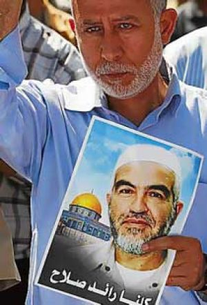 Palestinian Islamic Jihad leader Muhammed Al Hindi holds a picture of Sheik Raed Salah, the leader of the northern ...