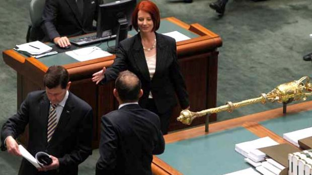 Prime Minister Julia Gillard enters Parliament for her first question time as Prime Minister and shakes hands with ...