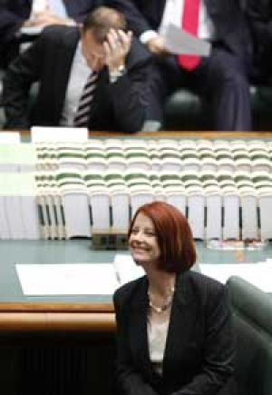 Winners are grinners ... Tony Abbott and Julia Gillard during question time in Parliament.