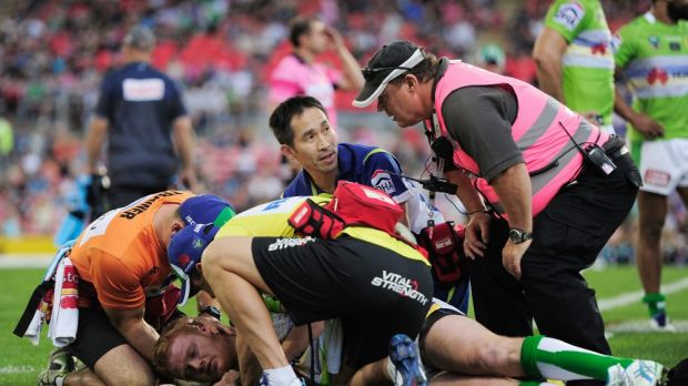 Raiders doctor Wilson Lo, centre, checks Joel Edwards after he was concussed against the Panthers.