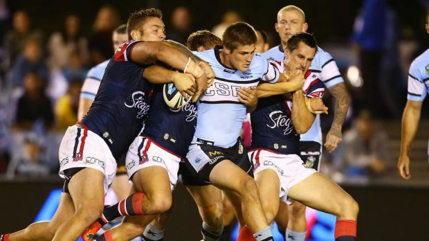 Sharks centre Blake Ayshford is rounded up by the Roosters' defence.
