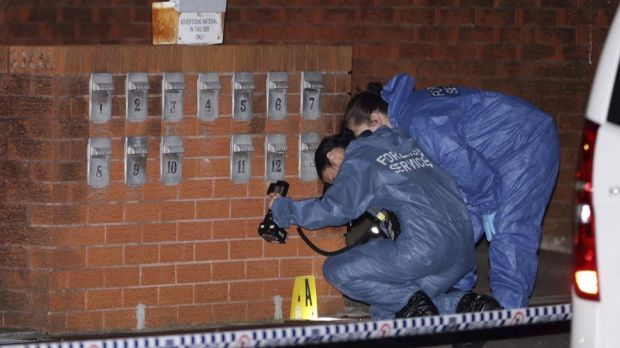 Forensic police photograph the scene outside the unit block.