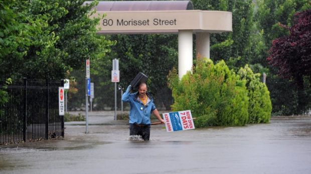 Dr David Poland leaves his flood-affected surgery in Morisset Street, Queanbeyan, during the 2010 flood.
