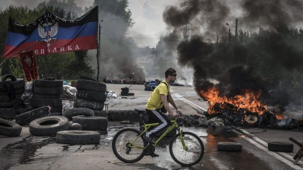 Dark days: a cyclist navigates a pro-Russian checkpoint left burning by Ukrainian troops advancing on the town of ...