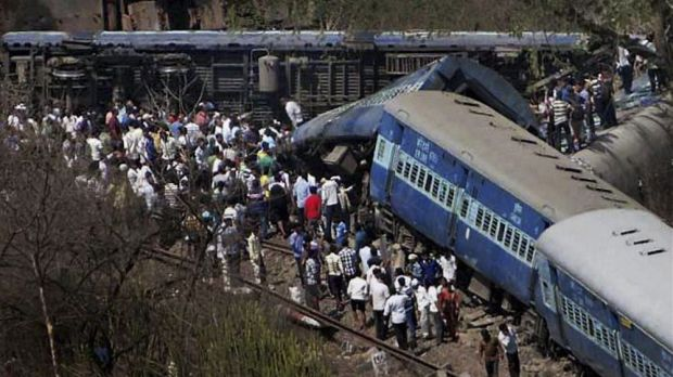 People gather around a passenger train that derailed near Roha station, 110 kilometres south of Mumbai.