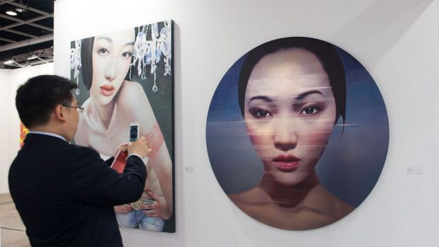 A visitor takes a photo of an artwork entitled 'Wind Angel' by Ling Jian on May 14, 2014 at the Hong Kong Convention and ...
