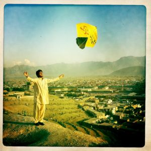 An Afghan man launches a kite from a ridge overlooking Kabul, Afghanistan.