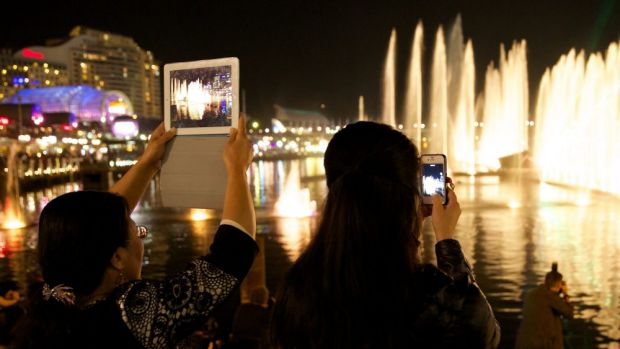 Audience members watch Vivid Aquatique Water Theatre at Darling Harbour on Wednesday. A man's body has been recovered ...