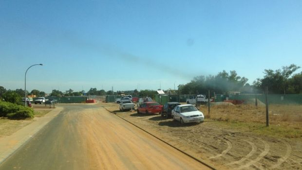 Houses, roads and pathways are coated in dust and dirt by trucks entering and exiting Gateway WA project to upgrade ...