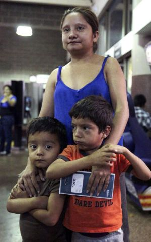 Floridalma Bineda Portillo, of Guatemala, and her sons wait at a bus terminal in Phoenix, Arizona. They were among 400 ...