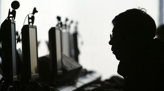 A computer user is silhouetted with a row of monitors at an Internet cafe in Shenyang, in northern China's Liaoning province.