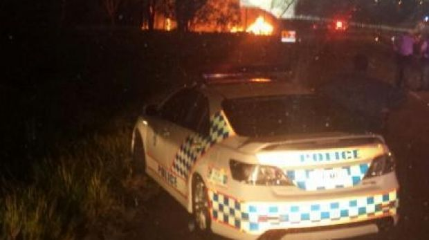 Police look on as a 4WD and police car burn following a police chase through Brisbane's north that ended at Deagon.