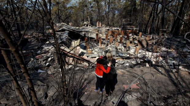 Amy Hubbard and her mum, Catherine, survey the ruins of the Winmalee home after it was destroyed during the October 2013 ...