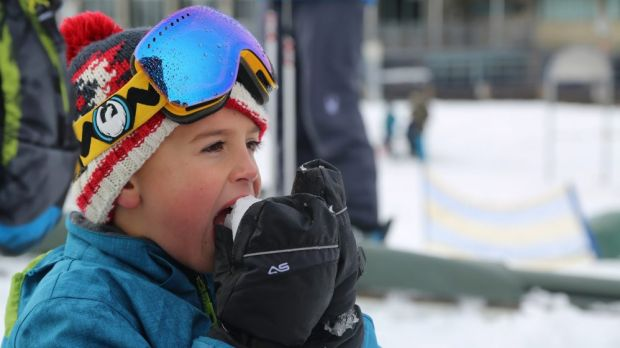 A kid at Perisher Blue appreciates the snow after 15 centimetres fell overnight.