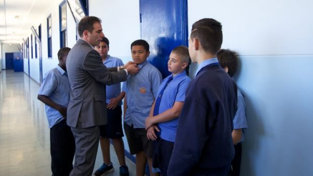 Principal of Punchbowl Boys High School Jihad Dib inspects the uniform of several students in the school corridor.