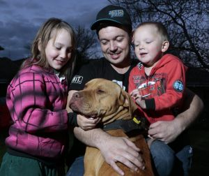 Justen Storay, centre, from Griffith with Zoe Storay, left, 8 and Declan Storay, right, 3 play with their family dog ...