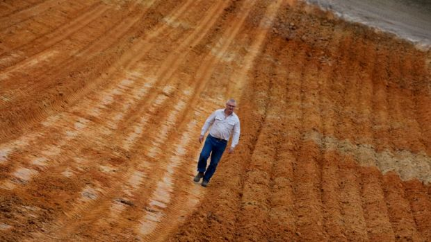 """Peter Nilon walks across a """"Claying Bed"""" one of the Hassad properties, a foreign-owned farm in far Western ..."""
