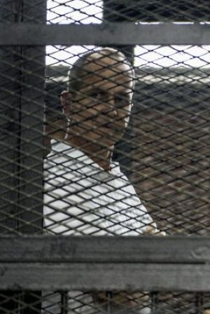 Peter Greste (left) listens to the verdict from the defendants' cage.
