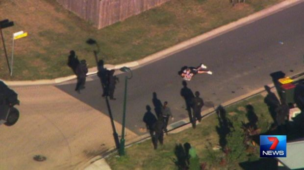 Police approach a man and child after a siege at Caboolture.