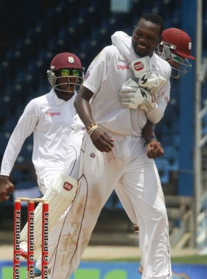 West Indies bowler Sulieman Benn is hugged by captain Denesh Ramdin, while celebrating the wicket of New Zealand's ...