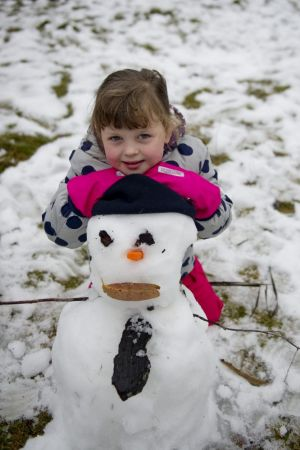 Isla Ozolin, 4, built a snowman at Corin Forest recreation park on Friday.