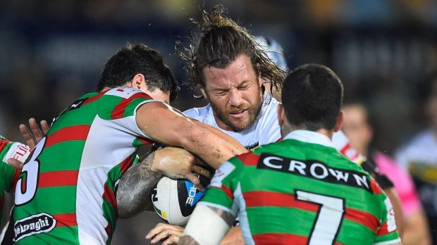 North Queensland veteran Ashton Sims is crunched by the South Sydney defence in Tonwsville.