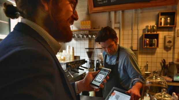 Sam Tate pays for his breakfast at Melbourne's The Little Mule Cafe using bitcoins.