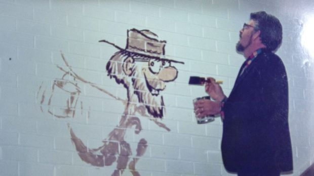 Rolf Harris paints the mural at Penhalluriack's Building Supplies in Caulfield in 1990.