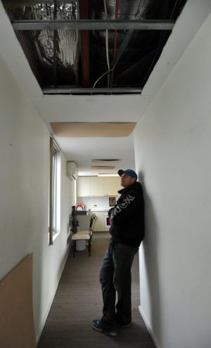 Gaping holes in the ceiling of Grant Seears' apartment are causing the heat to escape.