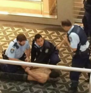 Restrained: Police subdue a man, 33, after a stabbing death at Westfield Parramatta.