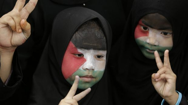 Filipino Muslims, with their faces painted with the colors of the Palestinian flag, flash peace signs during a rally ...