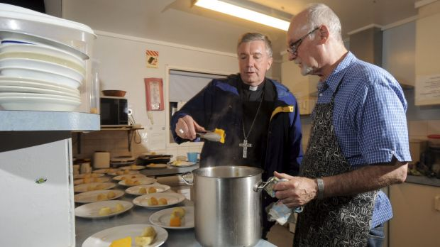 Catholic Archbishop of Canberra and Goulburn Christopher Prowse helps to dish out meals at the St Vincent de Paul ...