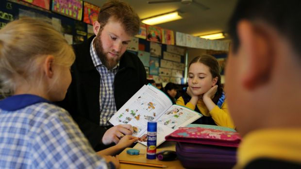 Michael Hanaghan shows a Latin textbook to Haberfield Public School students (from left) Elke Chapin, Mila Ossowaka and ...