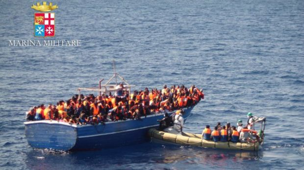 A handout picture from the Italian navy shows a boat full of migrants being picked up off the coast of Sicily.