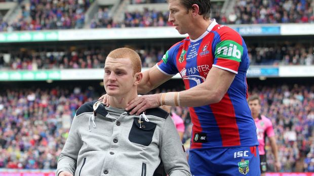 Kurt Gidley comforts Alex McKinnon before the start of the round 19 match between the Knights and the Titans.